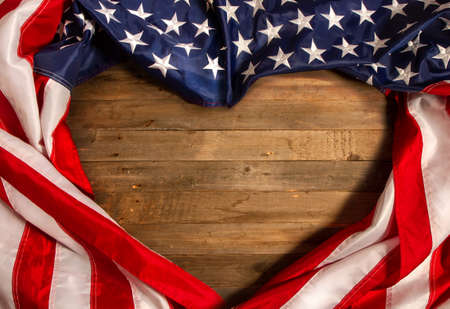 Star-striped flag of the United States of America stacked in the form of a heart on an old wooden background