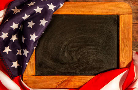 Stars and Stripes United States of America flag wrapped around an old chalkboard with a frame
