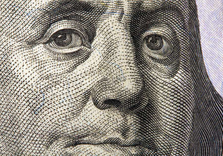 very close-up image of Benjamin Franklin's face on United States of America hundred dollar bill