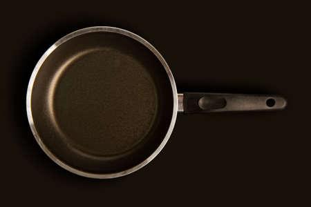 black steel empty frying pan with handle on dark surface