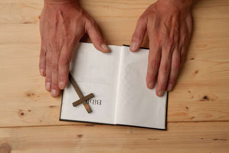 Man reading holy bible close-up on wooden background top view