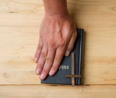 the hand of an adult man lies on the bible as a sign that he is telling the truth