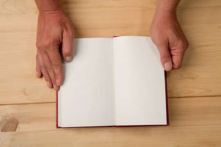 Male hands opened the page of a new book on a wooden background