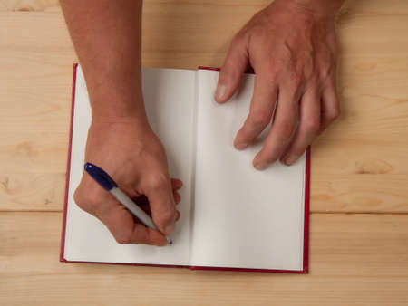 Male hands of the author who puts his autograph on a blank page in a new book