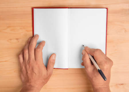 hands of the author giving autograph on the page of his book top view
