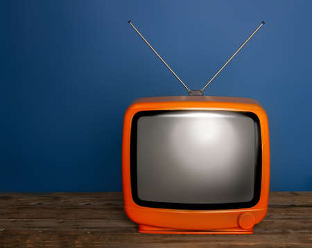 old bright vintage tv with blank screen and antenna on dark background