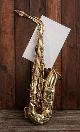 elegant classic musical instrument bronze saxophone on old wooden background with sheet of blank paper with place for text