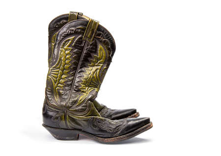 Shabby old ornate classic cowboy boots on wite background