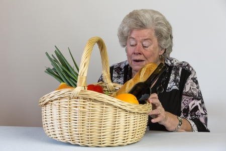 shopping basket: older lady looks at her shopping basket Stock Photo