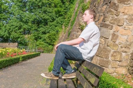 suns: Young man sits on a bank and suns himself