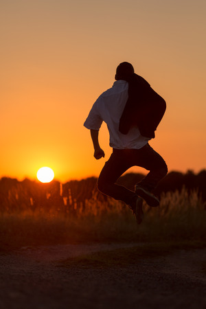 A lucky young man jumps in the sundown photo