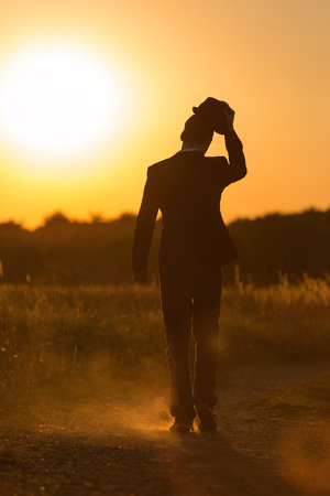 A young man with a hat walks in the sundown photo