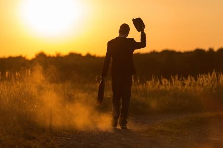 Een gelukkige jonge man met zak en hoed loopt in de zonsondergang Stockfoto