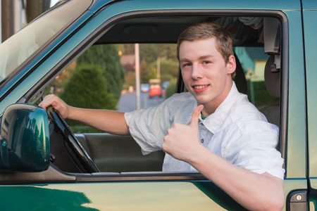 smile please: a young man sits in a car and smiles