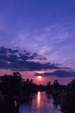 reflektion: An atmospheric sundown by the river Sieg in Rhineland, radiant orchid