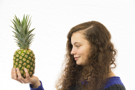 A young pretty woman holding a pineapple in the hand photo
