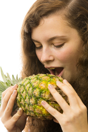 A young pretty woman biting into a pineapple photo