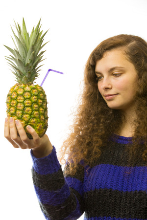 A young pretty woman holding a pineapple with straw in the hand photo