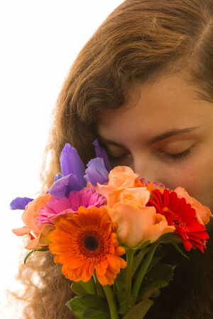 A young pretty woman holding a bunch of flowers and taking a smell photo