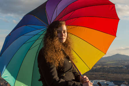 nicely: A young pretty woman sits with a coloured umbrella in the winter sun
