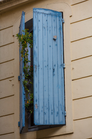 openly: A blue shutter on a yellow house wall with a flower behind it Stock Photo