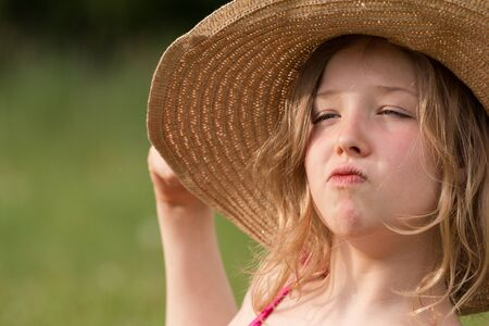 delightfully: A proud young girl with straw hat Stock Photo
