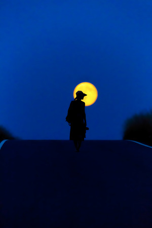 silueta humana: A woman walks a street at full moon