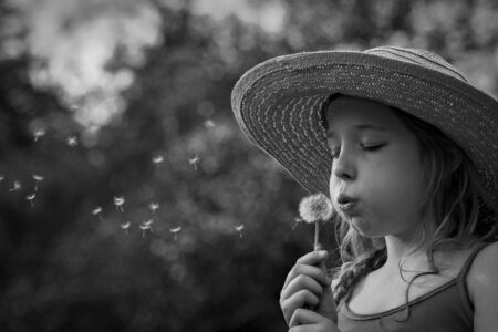 delightfully: Young girl blowing a dandelion