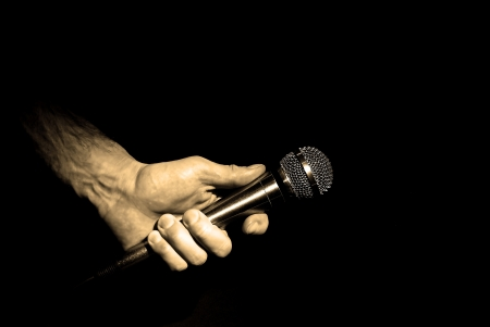 wedding guest: Image of hand holding microphone in light