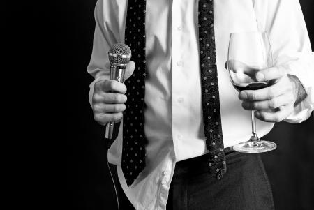 hablar en publico: Imagen de un hombre con un micr�fono y una bebida bien vestido