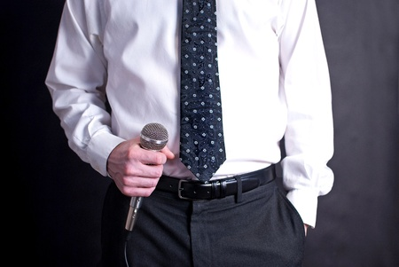 Image of a man holding a microphone and dressed nicely