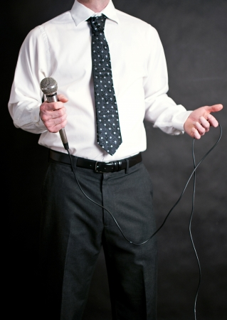 well dressed  holding: Image of a man holding a microphone and dressed nicely