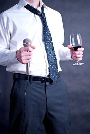 Image of a man holding a microphone and a drink dressed nicely Stock Photo