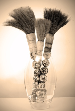 Image of several Chinese art paint brushes in a glass vase photo