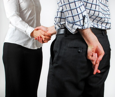 Image of two adults shaking hands with one of them crossing their fingers Stock Photo