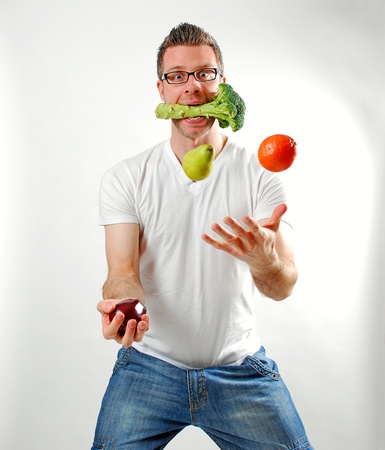 the calories: Image of a man juggling fruits and vegetables