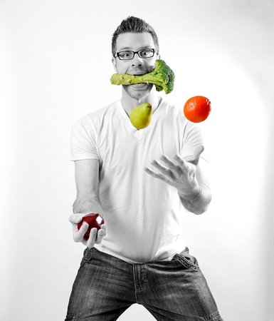 healthy choices: Image of a man juggling fruits and vegetables