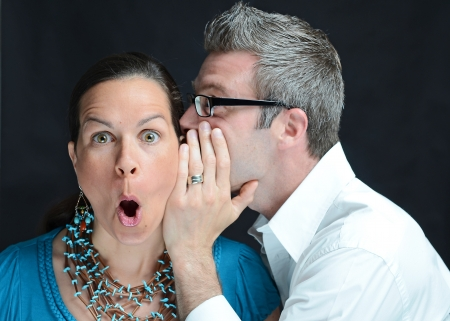 Image of a man telling a secret to a woman photo