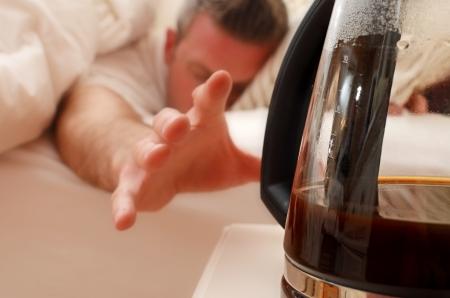 Der Griff nach einer Kaffeekanne aus dem Bett Standard-Bild - 14170723