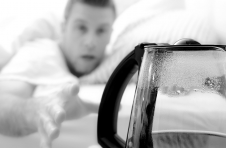 Reaching for a coffee pot from bed Stock Photo - 14170722
