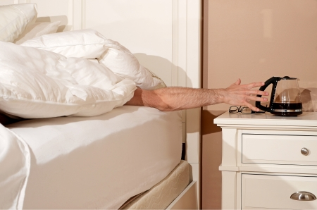 Image of someone reaching for a coffee pot from bed