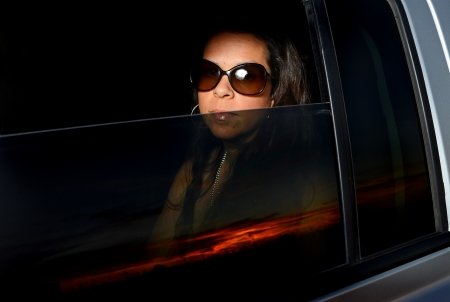 Image of an attractive female looking through a vehicle window Stock Photo