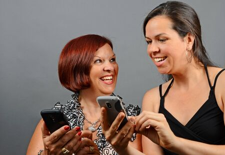 Image of a mother and daughter having fun on their phones photo