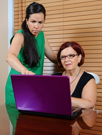 Image of a young lady using a laptop with an older lady photo