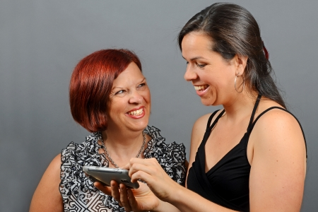 Image of a mother and daughter having fun on their phones