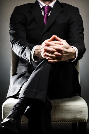 kracht: Man met pak zittend Stockfoto