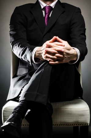 body language: Man Wearing Suit Sitting Stock Photo