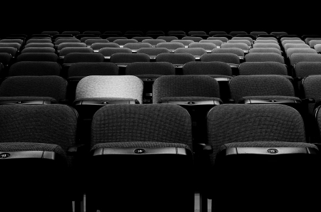 Image of many rows of seats with a spotlight on one
