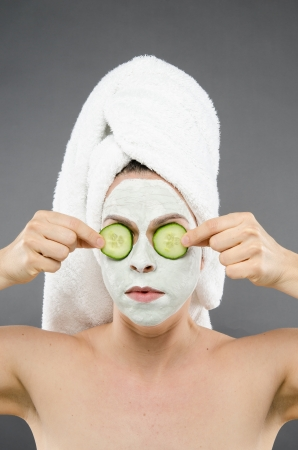 Image of a woman holding cucumbers over her eyes for a beauty treatment
