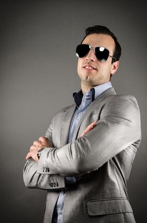 lenguaje corporal: Joven vistiendo traje y gafas de sol